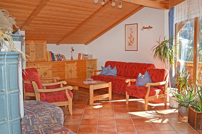 Aufenthaltsraum mit Kachelofen, kleiner Bibliothek und Balkon - Bacherhof