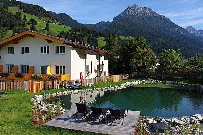 Großer Naturschwimmteich mit Liegewiese, im Hintergrund Nebengebäude mit Fewo