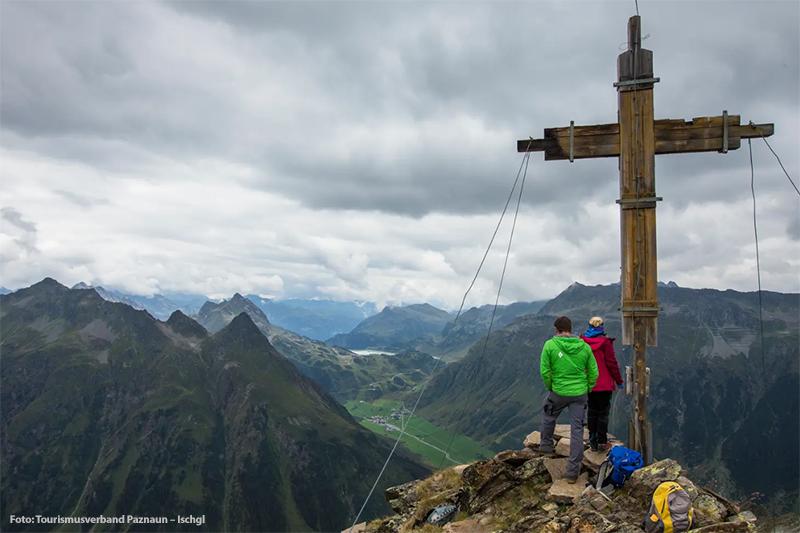 Wanderer und die Aussicht beim Gipfelkreuz in Galtür genießen