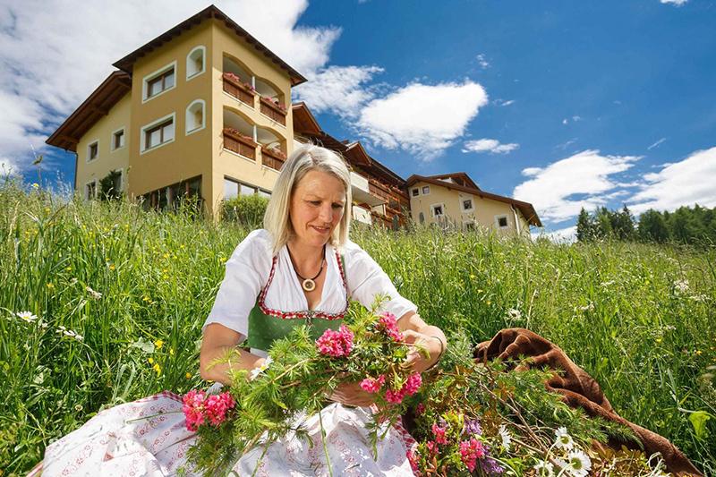 Monika von der Gastgeberfamilie Egger liebt ihre Blumen auf der Wiese vor dem Wohlfühlhotel Falzeben in Südtirol