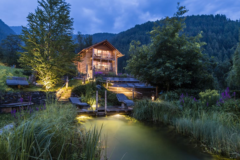 Auch am Abend ein genussvolles Erlebnis: Das Badehaus und der Badeteich mit Alpingarten im Natur- und Wellnesshotel Lüsnerhof in Südtirol