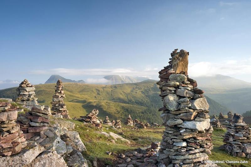 Stoanerne Mandln im Wandergebiet Meran 2000 - an diesem einzigartigen Ort reihen sich über 100 Steinfiguren aneinander - in ihrer Mitte das Gipfelkreuz. Was es mit diesen Figuren auf sich hat und wie sie entstanden sind, ist immer noch rätselhaft…