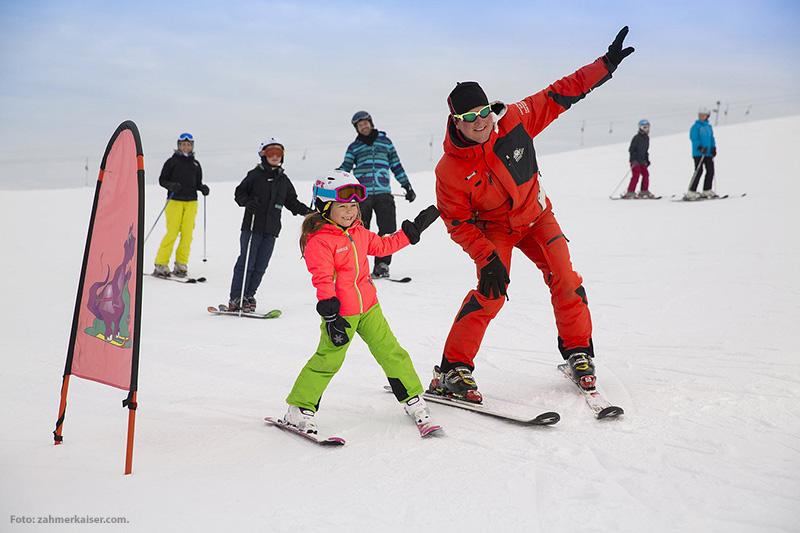 Skilehrer mit jungem Skifahrer auf der Piste
