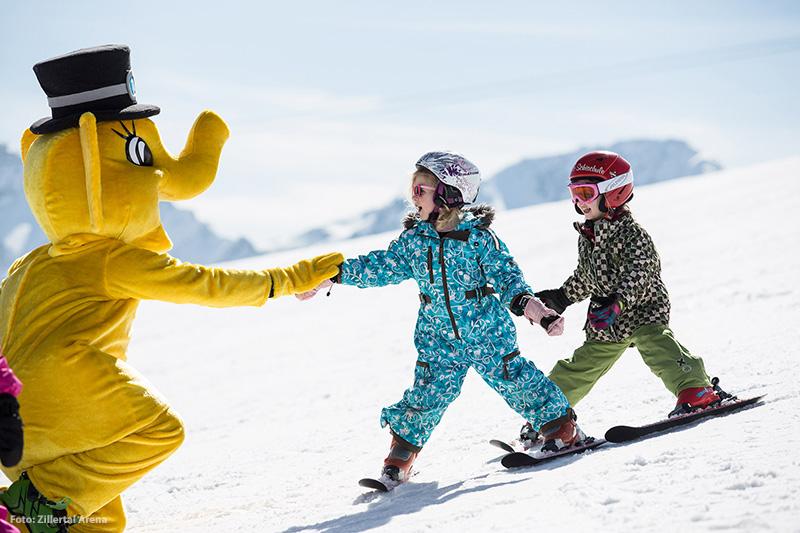 Kleine Skifahrer mit Maskottchen