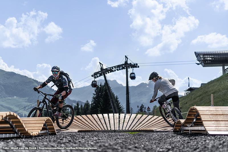 Biker nutzen das Fahrtechnik- und Übungsgelände Pumptrack an der Reiterkogelbahn Bergstation